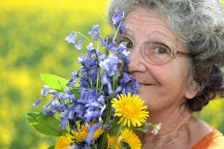 flowers next to face and smiling
