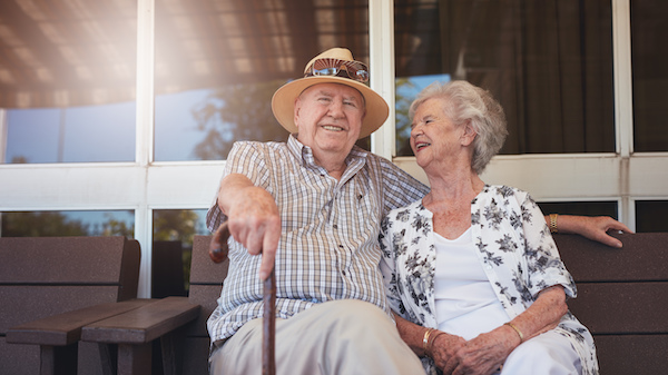 elderly couple sitting outside on a sunny day