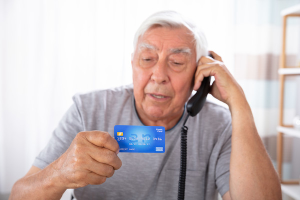 Close-up Of A Senior Man With Credit Card Using Landline Phone