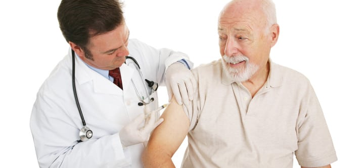 Senior man getting a flu shot from his doctor.